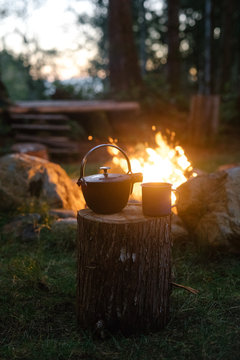 a campfire with a cast iron kettle and enamel cup