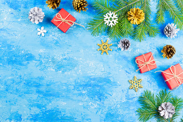 Blue Christmas background with fir branches, red giftboxes, silver and golden decorations, copy space