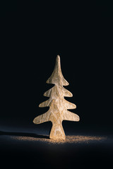 Mini golden Christmas tree with glitter on black background