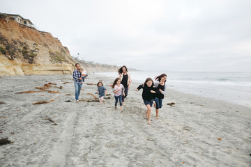 Family of seven running together on beach