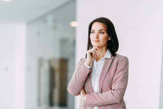 Beautiful business girl on light office background. Business coach and coach of success.