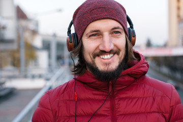 Young handsome bearded man posing outdoor in cold wind weather on the street in red hat and jacket with vintage style earphones listening music
