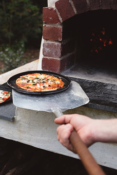outdoors cooking pizza in wood fire oven
