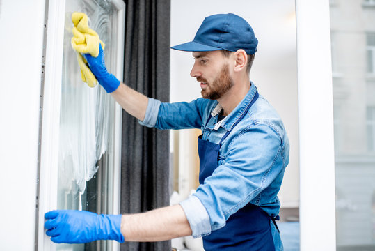 Man as a professional cleaner in blue uniform washing window with cotton wiper indoors