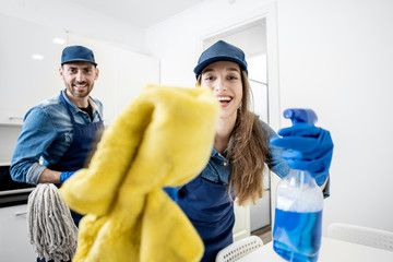 Funny portrait of a man and woman as aprofessional cleaner with cleaning tools in the white apartment interior