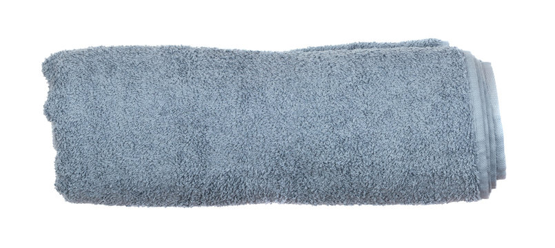 Gray rolled or folded hotel towel isolated on white close up
