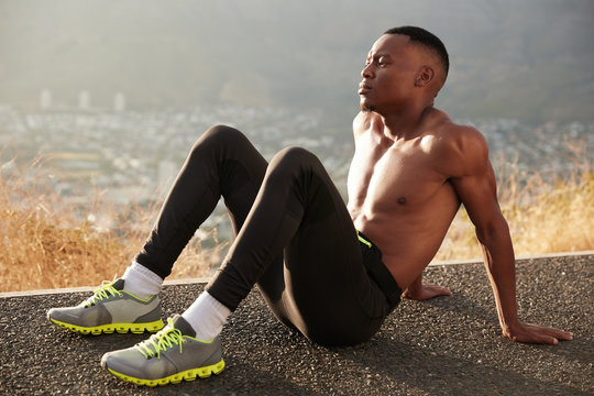 Horizontal view of pensie black male leans at hands, sits on road, models against foggy blurred background, has muscular body, wears sport leggings, trainers, white socks. Jogging in open air