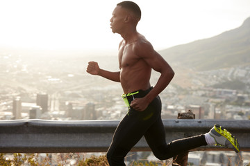 Fitness, health and jogging concept. Sideways shot of motivated black young male runs on mountain road in nature, enjoys fresh air outside, wears sportshoes and activewear, sees finish in distance.