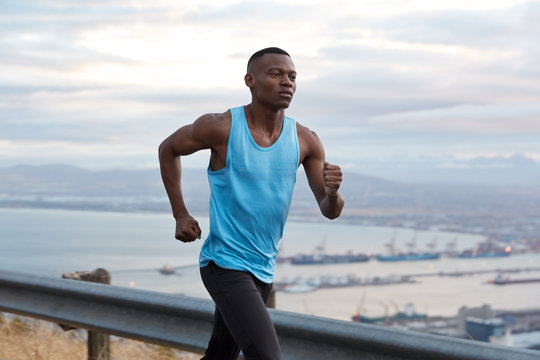 Outside shot of confident Afro American fitness male has goal achievement challenge to reach destination without break, works actively with hands, dressed in sportswear, joggs over nice nature view