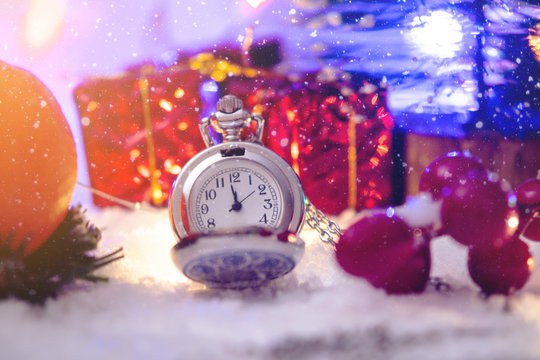 Pocket watch with a dial in the snow with gifts on the eve of holidays. Waiting for the magic of Christmas and new year