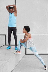 African American male adult raises hands, warms up before cardio training. Dark skinned woman in leggings and sneakers stretches legs, prepares for jogging marathon. Two sporty people at stairs