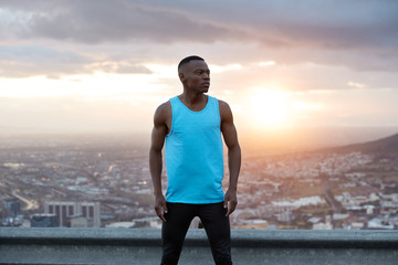 Panoramic view of free black muscular man in activewear, has outdoor exercises, poses over beautiful landscape, sunrise at dawn, city buildings, clear sky, enjoys freedom, fresh air and loneliness