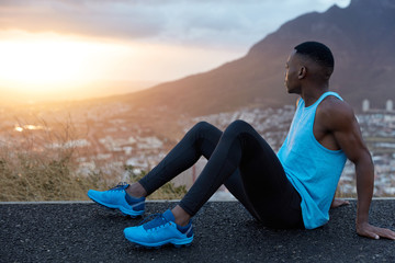 Fitness male sits sideways, has black skin, muscular hands, dressed in sportswear, looks attentively at sunrise, poses over mountains background, takes break after intensive running. Sport, nature