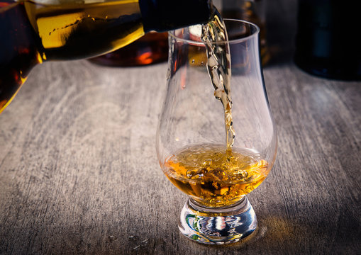 Pouring single malt scotch whisky into whisky glass on wooden table