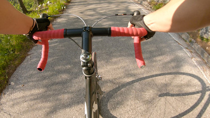 POV: First person shot of pedalling a bicycle up a hill in the sunny mountains.