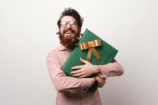 Smiling bearded man holding big gift box for christmas over white background