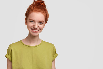 Image of pretty red haired girl has charming smile on face, wears casual green t shirt, feels happy, isolated over white studio wall with free space for your advertising content or promotion. Emotions