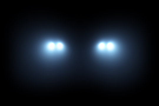 Car head lights shining from darkness background