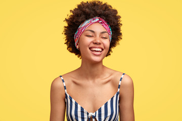 Joyful dark skinned model laughs pleasantly, closes eyes from happiness, recieves wonderful suggestion, being in high spirit during summer trip, wears headband and striped top, poses indoor.