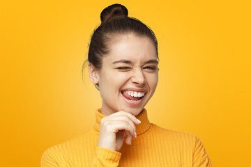 Beautiful girl in bright yellow polo neck sweater. smiling and winking to camera