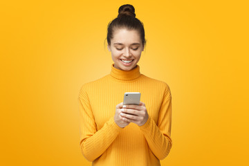 Yong pretty female standing isolated on yellow background looking at screen of phone, smiling...