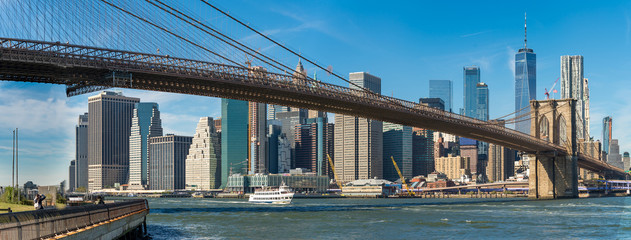 Panoramic view of Brooklyn bridge over Manhatten skyscrapers in New York.