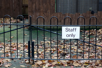 Staff only sign at workplace fence gate