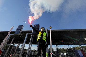 A fireman holds a safety flare as he joins protesters wearing yellow vests, a symbol of a French drivers' protest against higher diesel fuel prices, during a demonstration at the motorway toll booth in Antibes
