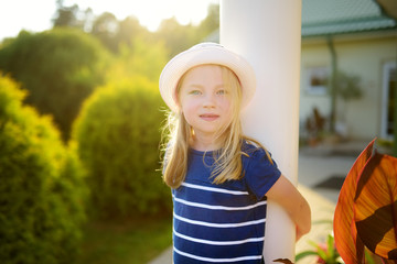 Cute little girl wearing straw hat having fun on the backyard on sunny summer evening.