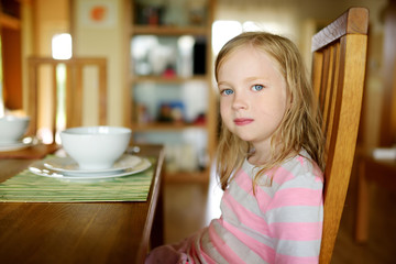Cute little girl eating a soup in cozy dining room. Child having a dinner at home.