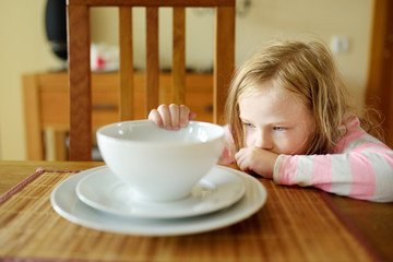 Cute little girl unwilling to eat her soup. Child having a dinner at home.