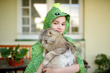 Cute girl wearing fancy costume holding her cat on sunny summer day. Adorable child holding het pet kitty.