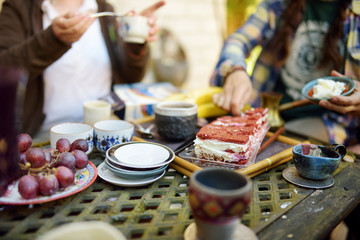 Beautiful dessert table with colourful ceramic cups, saucers, delicious carrot cake and fruits. Eating sweets and desserts outdoors.