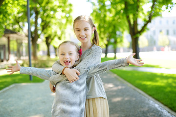 Two adorable sisters laughing and hugging on warm and sunny summer day in a park.