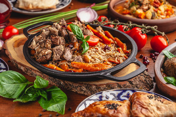 The concept of Uzbek, oriental cuisine. Pilaf in a cast-iron pan, with pieces of lamb lies on a wooden table. Festive table set.