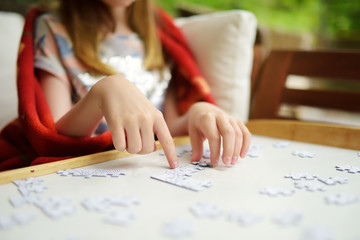 Close-up on child's hands assembling a jigsaw puzzle on a table