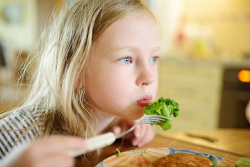 Cute little girl eating broccoli in cozy dining room. Child having a dinner at home.