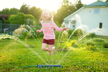 Adorable little girl playing with a sprinkler in a backyard on sunny summer day. Cute child having fun with water outdoors.