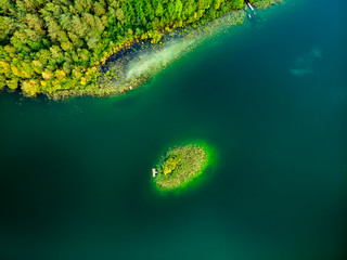 Aerial top down view of small island. Birds eye view of beautiful green waters of lake Gela surrounded by pine forests, near Vilnius city, Lithuania.