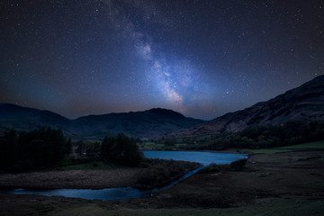 Vibrant Milky Way composite image over landscape of Lake District landscape in England