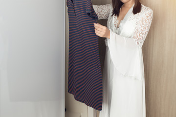 Asian woman in long white nightgown choosing clothes in wardrobe at home