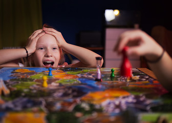 Board game concept - your move. Little girl watched the game and shock from the action move. Board game field, many figures. Kid girl play in board game at home on dark blurred background