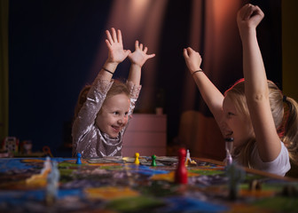 Board game concept.Two little girls spend fun time at home playing board games. Board game field, many figures, two kid girls play in board game at home on dark blurred background