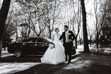 Bride and groom take photos near a black car. Black and white picture.