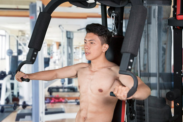 Muscular man exercising with fitness machine