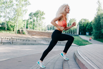 Photo of curly-haired athletic woman running through park among
