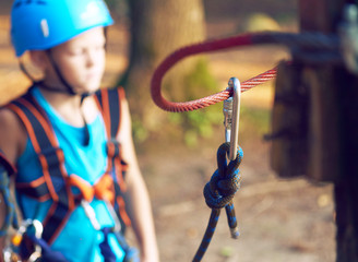 Cute little boy in blue shirt and helmet having fun at the adventure park, holding ropes and prepering to climb wooden stairs. Hobby, active lifestyle concept.