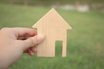 Hand holding Wood house model on nature background,Choosing the right real estate property, or new home in a housing development or community