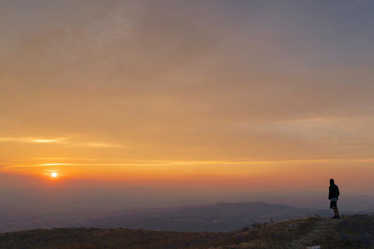 Silhouette of man watching the sunset from the top of a mountain