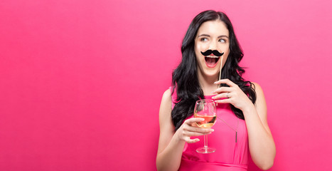 Young woman holding champagne flute and paper party stick